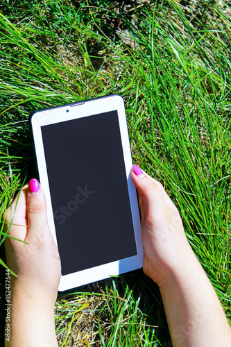 woman s hands holding white tablet with blank skreen on green grass