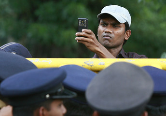 A demonstrator uses his camera phone to take photographs of policemen during a protest in Colombo