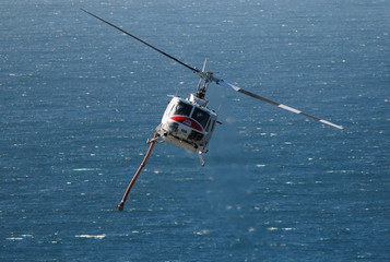 A Cal Fire helicopter flies towards Garrapata State Park after picking up water from the Pacific Ocean during the Soberanes Fire north of Big Sur