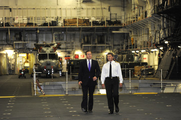 British Prime Minister David Cameron is escorted by Captain Andrew Betton in the hangar of HMS Ocean on the River Thames