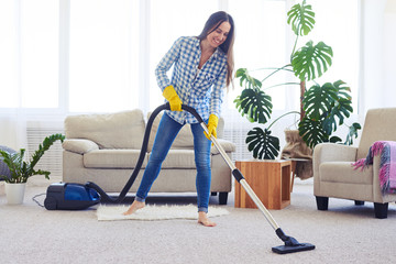 Slim woman cleaning with vacuum cleaner carpet