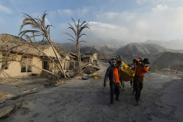 Volunteers carry the body of a victim of the Mount Merapi eruption at Kinarrejo village in Sleman