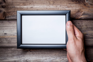 Male hands holding empty copy space black photo frame.