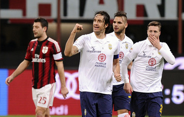 Hellas Verona's Toni celebrates with his team mates Tachtsidis and Sala after scoring against AC Milan during their Italian Serie A match in Milan