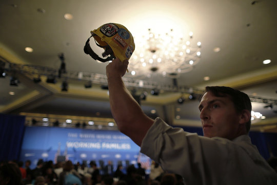 Brooks of IBEW Local Union 617 holds aloft a worker's hardhat as participants take their seats for the White House Summit on Working Families in Washington
