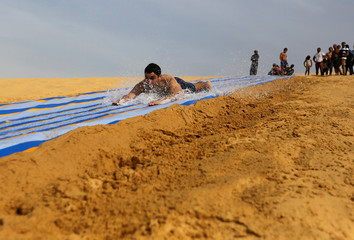 A man slides down a ramp into the lake in Wadi el-Rayan Fayoum