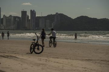 Pessoas pedalando na areia da praia