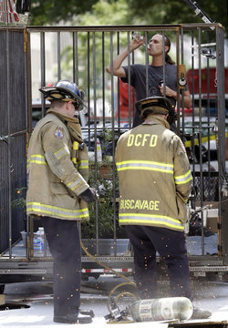 David Bronner drinks beer as firefighters cut him out of a steel cage from which he was staging a protest, in front of the White House in Washington