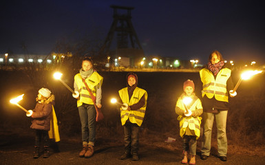 A demonstrator and children form part of a chain of lights during a protest in front of the Schacht Konrad nuclear depot in Bleckenstedt near Salzgitter