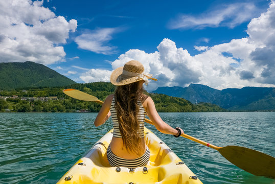 Young woman with long hair and hat kayaking in sun on lake