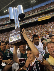 Fluminense's Conca celebrates with a fake trophy after winning the Brazilian soccer championship against Guarani in Rio de Janeiro