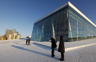 Pedestrians walk around the Opera House during winter in Oslo