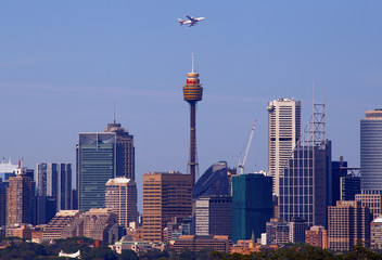 An Emirates Airlines Airbus A380 plane flies above Sydney's central business district after taking off from Sydney International Airport in Australia