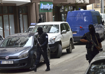 Masked police officers carry their weapons as they stand guard in front of a court in Pristina