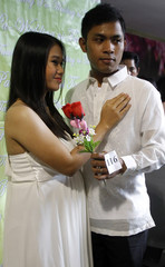 A seven-month pregnant bride poses for a picture with her groom before the start of a mass wedding ceremony as part of a Valentine's Day celebration in Paranaque