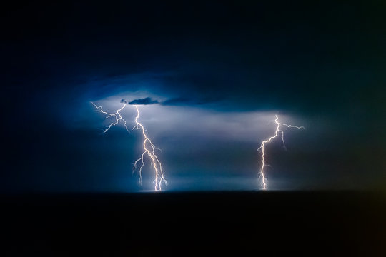Dual bright lightning that goes into depth of black sea, with branching branches in different directions, which illuminate the southern coast of Crimea and Yalta, at night, over in the sky