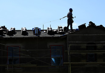 A construction worker installs a roof on a home in a new subdivision being built in San Marcos, California