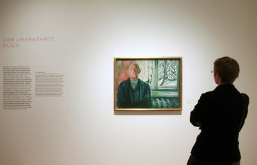 """A visitor looks at the painting """"Self-Portrait by the Window"""", circa 1940 by Norwegian artist Edvard Munch presented at an exhibition in Frankfurt"""
