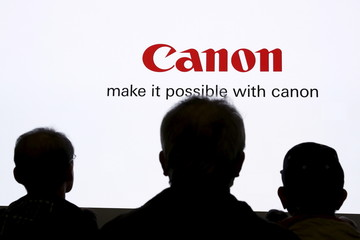 People are silhouetted against a display of the Canon brand logo at CP+ camera and photo trade fair in Yokohama