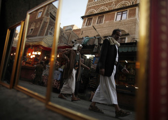 People are reflected in mirrors put on display for sale on a street in the Old Sanaa city