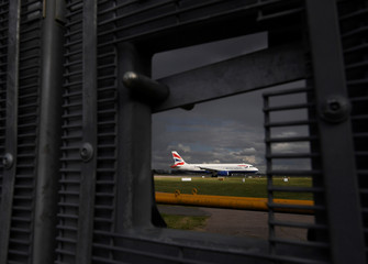 A British Airways passenger aircraft  is seen through a perimeter fence gate as it prepares for take off from Gatwick Airport in southern England, Britain