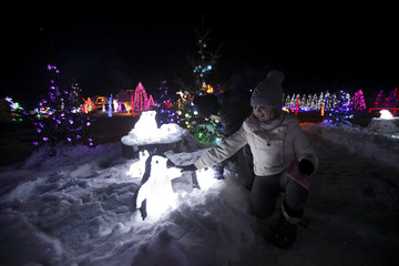 Children play with decorative penguins at a country house estate in the village of Grabovnica
