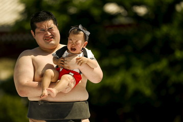 Amateur sumo wrestler holds baby during baby crying contest at Sensoji temple in Tokyo