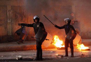 Riot police walk past burning tyres placed to form a barricade during clashes in Cairo