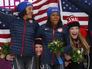 Canada's Humphries and Moyse celebrate with Myers and Williams of U.S. during flower ceremony for women's bobsleigh event at 2014 Sochi Olympic Games