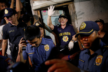 Policemen try to maintain order outside a house in which five people were killed in Manila