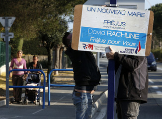 Supporters install a campaign poster to support David Rachline, France's National Front head of the list for municipal elections, in Frejus