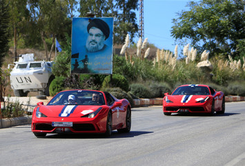 Ferrari cars travel past a UN vehicle and a picture of Lebanon's Hezbollah leader Sayyed Hassan Nasrallah during a Ferrari ride around Lebanon, near the Lebanese-Israeli border in Kfar Kila village