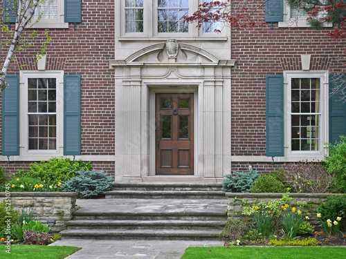 Front Door With Stone Steps And Spring Flowers Stock Photo