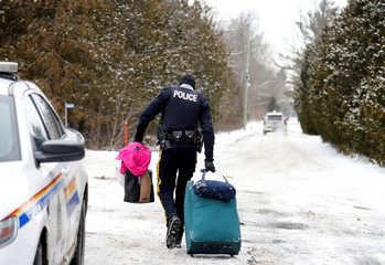 A Royal Canadian Mounted Police officer carries luggage of a woman and her family who told police they were from Sudan and were taken into custody after arriving by taxi and walking across the U.S.-Canada border into Hemmingford, Quebec