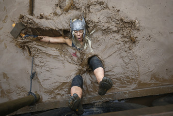 Competitor falls in to muddy water during the Tough Guy event in Perton