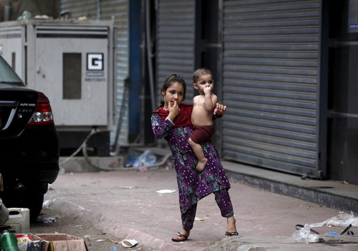 A Pashtun girl carries her sibling while standing near her family home during a power outage in Karachi,