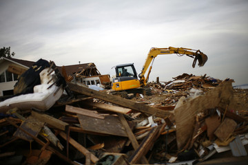 A worker removes the debris of a home destroyed by Hurricane Sandy in Union Beach