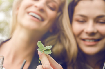 two sisters or friends hold four-leaf clover and dream of happiness