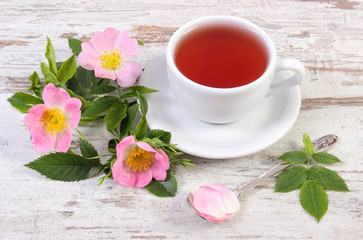 Cup of hot tea and wild rose flower on rustic wooden background