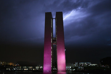 Brazil's National Congress headquarters is illuminated with pink lights as lightning is seen in Brasilia