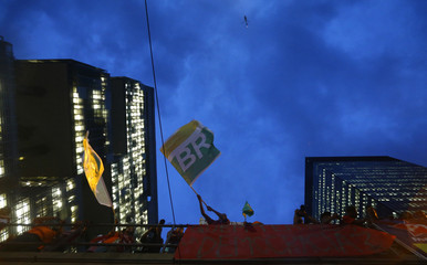 Workers wave flags with Petrobras' logo as they take part in a demonstration in defense of Brazil's President Dilma Rousseff and the state-run oil company, in front of the Petrobras headquarters in Rio de Janeiro