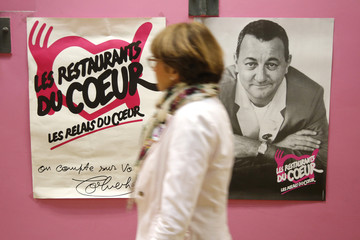 "A woman walks past a picture of late French comic Coluche at a food distribution centre for the ""Les Restos du Coeur"" (Restaurants of the Heart) in Paris"
