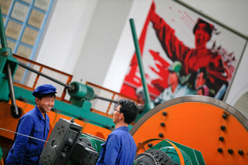 Workers are photographed during a government organised visit for foreign reporters to the Pyongyang 326 Electric Cable Factory in Pyongyang