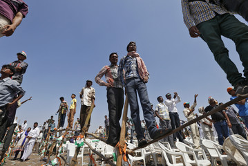 Supporters of the Congress party, stand on poles to get a glimpse of Rahul during an election campaign rally in Gujarat