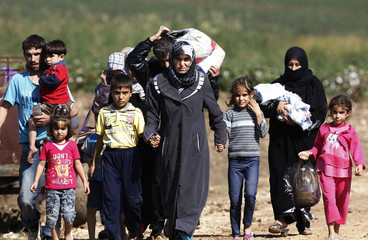 Syrians walk after crossing to Turkey by boat on the Orontes river of the Turkish-Syrian border near the village of Hacipasa
