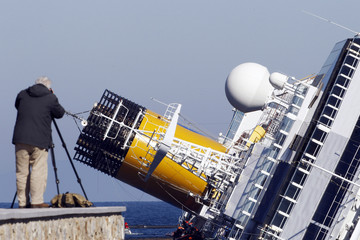 A man takes a picture of the cruise liner Costa Concordia, which ran aground off the west coast of Italy, at Giglio island