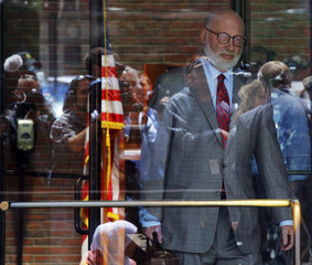 """Reporters and television cameras are reflected in the glass doors as J.W. Carney, defense attorney for accused mob boss James """"Whitey"""" Bulger, leaves the U.S. Federal Courthouse at the end of first day of Bulger's trial in Boston"""
