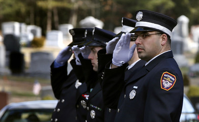 Firefighters salute as the funeral procession of seven-year-old Daniel Barden, killed in the December 14 shootings at Sandy Hook Elementary School, arrives at the Saint Rose of Lima Parish cemetery in Newtown