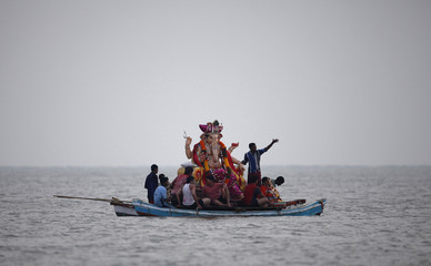 Devotees carry an idol of the Hindu elephant god Ganesh on a boat as they take it for immersion into the Arabian Sea on the last day of the Ganesh Chaturthi festival in Mumbai