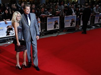 U.S. actor David Hasselhoff and Hayley Roberts pose for photographers as they arrive for the world premiere of the film Larry Crowne at Westfield in London